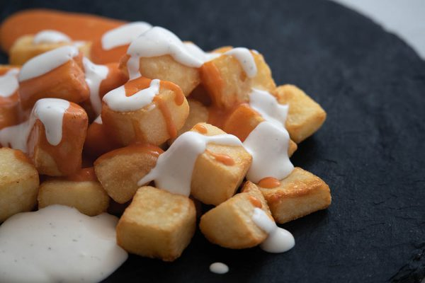 Ración de patatas bravioli en Malasaña
